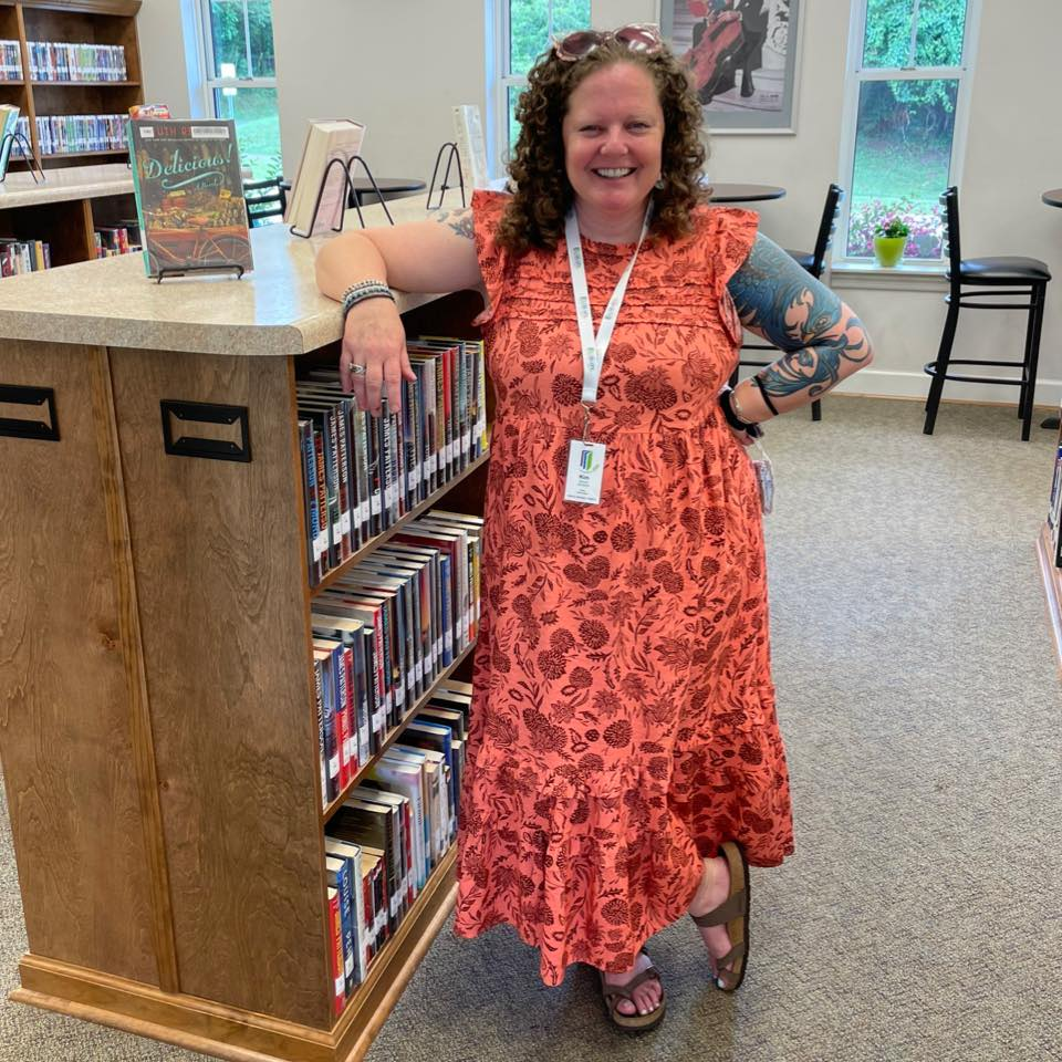 Kim standing next to library shelves